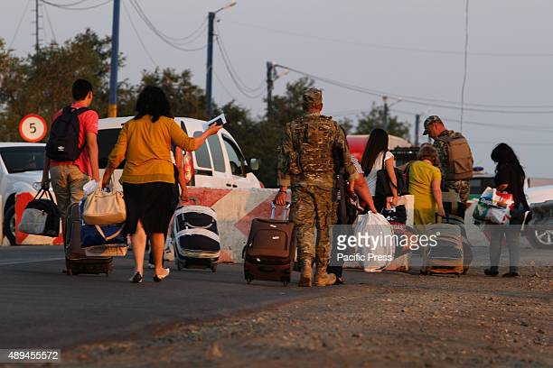 People carrying their goods across the border between the mainland of Ukraine and the annexed territory of Crimea Chairman of the Mejlis of the...