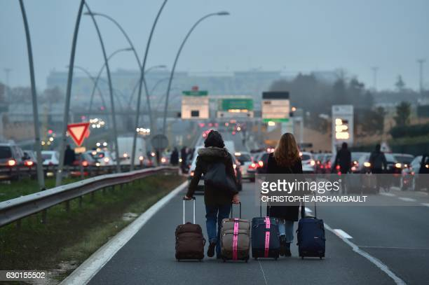 People carrying their luggages walk past French antiriot police officers on the highway leading to the Orly airport on December 17 2016 as VTC...