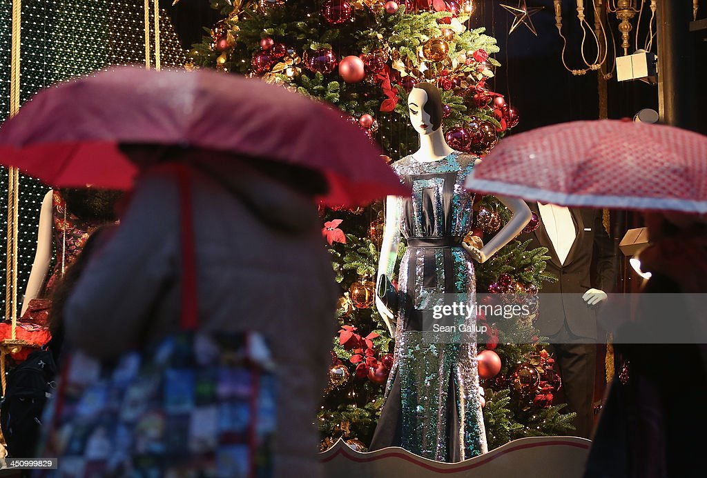People carrying umbrellas walk past a Christmas shop window display at the KaDeWe department store on Kurfuerstendamm avenue on November 20, 2013 in Berlin, Germany. Berlin, with still over a month to go, is preparing for Christmas.