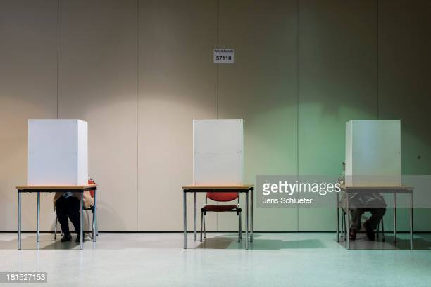 People cast their ballots in German federal elections at a culture center on September 22 2013 in Halle Germany Germany is holding federal elections...