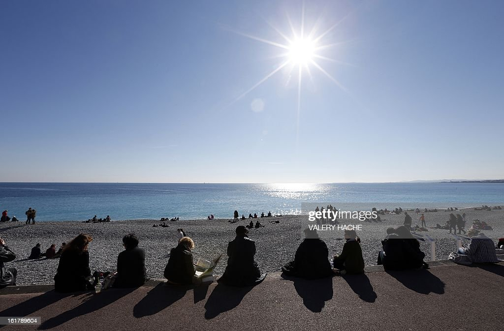 People catch some rays of sun on the Mediterranean sea on February 16, 2013 in the southeastern French city of Nice. AFP PHOTO / VALERY HACHE