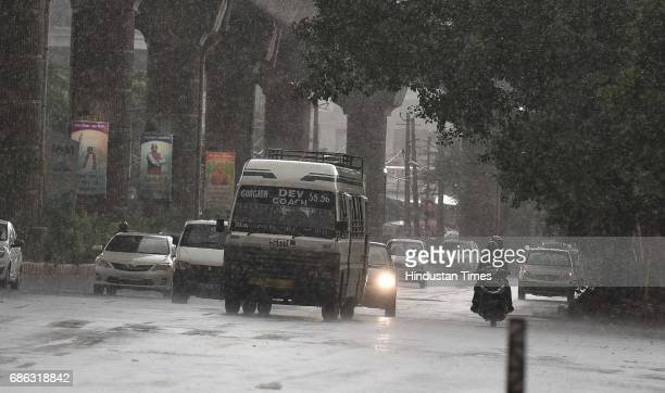 People caught in a sudden heavy rainfall and dust storm at MG Road on May 21 2017 in Gurugram India Heavy rainfall lashed Delhi/NCR evening bringing...