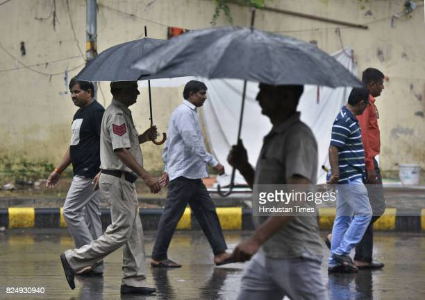 People caught in the light rain at Jantar Mantar on July 31 2017 in New Delhi India Delhiites woke up to a drenched morning as rains hit the city on...