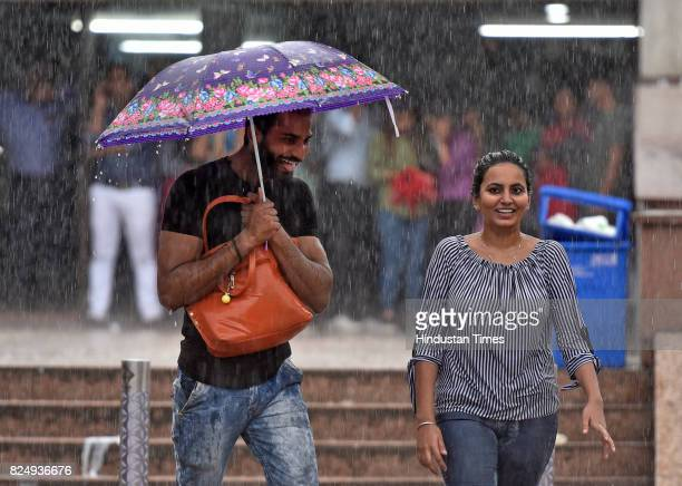 People caught in the monsoon rain at Connaught Place on July 31 2017 in New Delhi India Delhiites woke up to a drenched morning as rains hit the city...