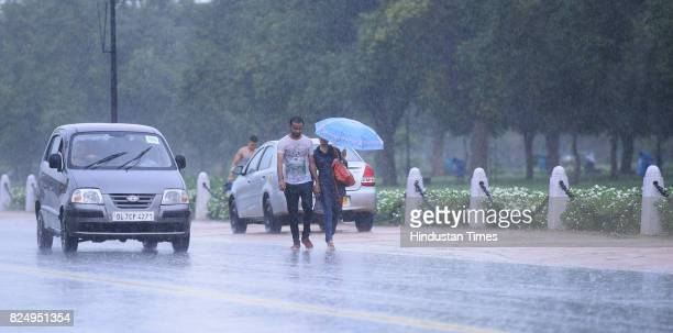 People caught in the monsoon rain at India Gate on July 31 2017 in New Delhi India Delhiites woke up to a drenched morning as rains hit the city on...