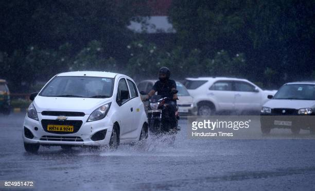 People caught in the monsoon rain at Mandi House on July 31 2017 in New Delhi India Delhiites woke up to a drenched morning as rains hit the city on...