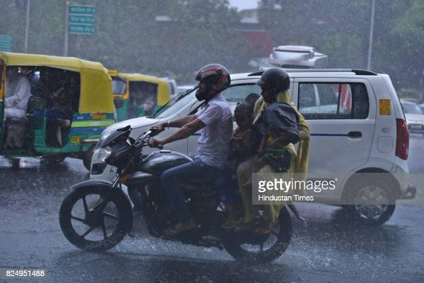 People caught in the monsoon rain at Mandi House on July 31 2017 in New Delhi India Delhites woke up to a drenched morning as rains hit the city on...