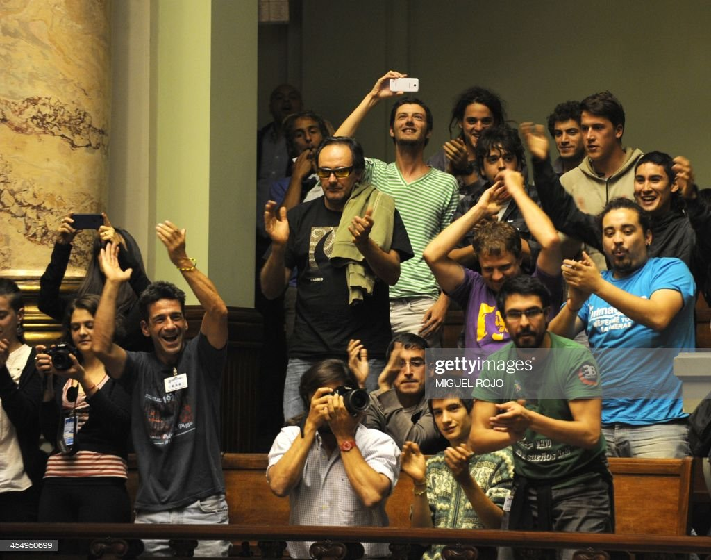 People celebrate after the Uruguayan senate approved a law legalizing marijuana in the Legislative Palace in Montevideo, on December 10, 2013. The initiative launched by 78-year-old Uruguayan President Jose Mujica, a former revolutionary leader, will enable the production, distribution and sale of cannabis, self-cultivation and consumer clubs, all under state control. AFP PHOTO/ Miguel ROJO