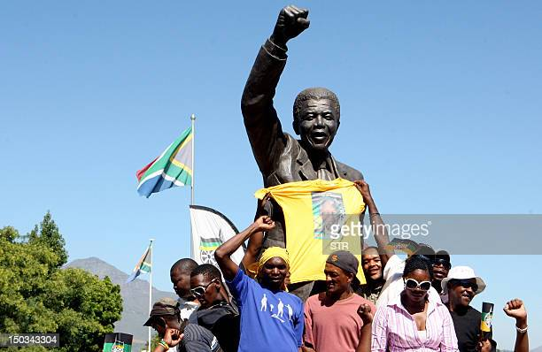 People celebrate at statue of Nelson Mandela outside the gates of Groot Drakenstein formerly Victor Verster jail outside of Paarl to commemorate...