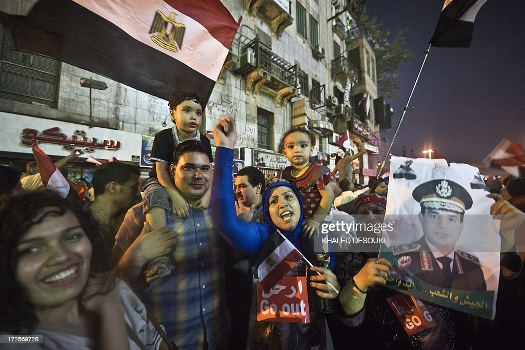 People celebrate at Tahrir Square with a portrait of Army chief Abdel Fattah alSisi after a broadcast confirming that the army will temporarily be...
