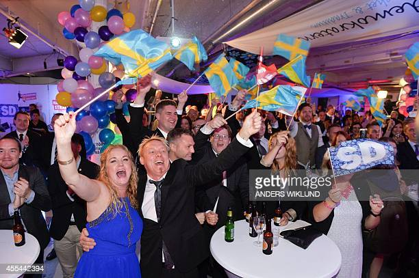 People celebrate at the election night party of the farright Sweden Democrats in Stockholm Sweden after first exit polls indicate that the party will...