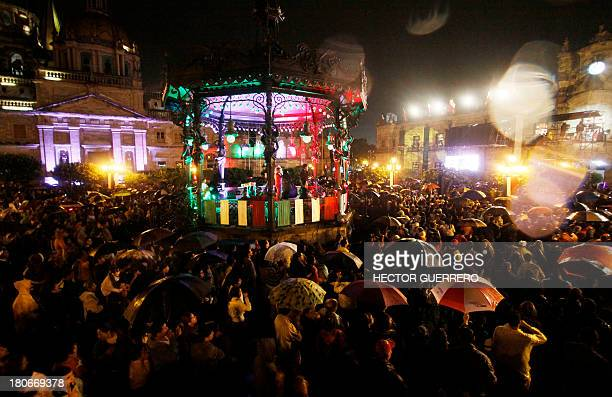 People celebrate below the rain during celebrations for Mexico's Independence Day at the Armas Square in Guadalajara City on September 15 2013...