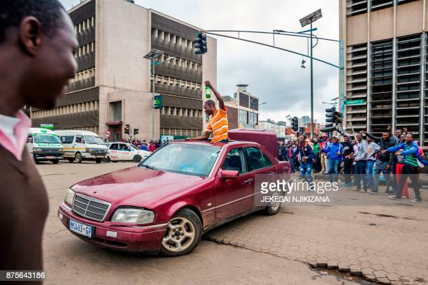 TOPSHOT People celebrate during a demonstration demanding the resignation of Zimbabwe's president on November 18 2017 in Harare Zimbabwe was set for...