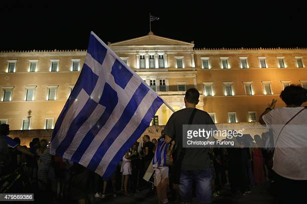 People celebrate in front of the Greek parliament as early opinion polls predict a win for the Oxi campaign in the Greek austerity referendum Crowds...