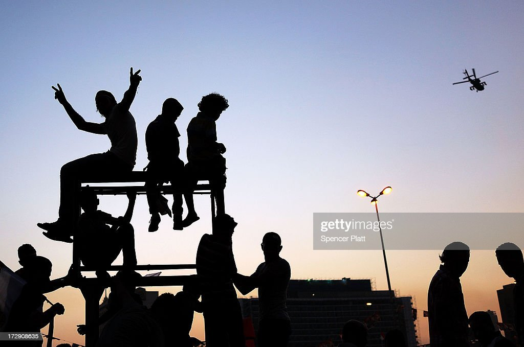 People celebrate in Tahrir Square as a military helicopter flies overhead following the ousting of former President Mohammed Morsi by the Egyptian...
