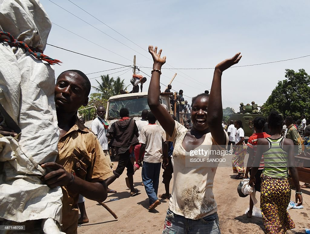 People celebrate, on April 27, 2014 in Bangui, after about 1.300 Muslims who were hiding in the PK12 district left in a convoy escorted by the Misca African force, to be relocated in the north of the country.