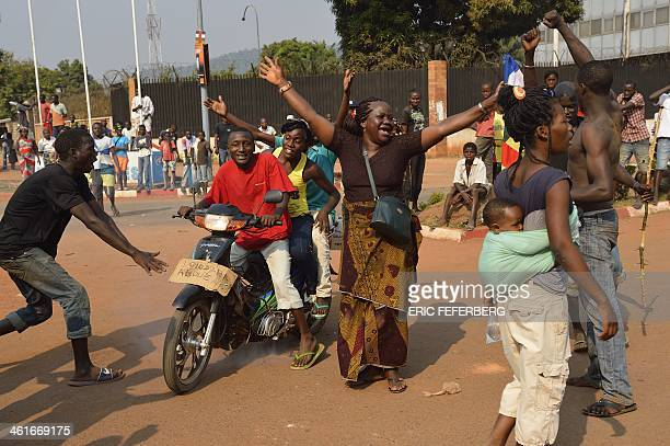 People celebrate on January 10 2014 in Bangui after the announcement of the resignation of Central African Republic President Michel Djotodia under...