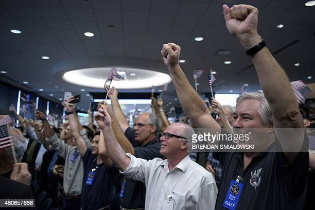 People celebrate the closest flyby of NASA's New Horizons probe at the Johns Hopkins University Applied Physics Laboratory July 14 2015 in Laurel...