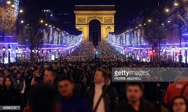 People celebrate the New Year on the ChampsElysees in Paris on early January 1 2014 AFP PHOTO / PIERRE ANDRIEU