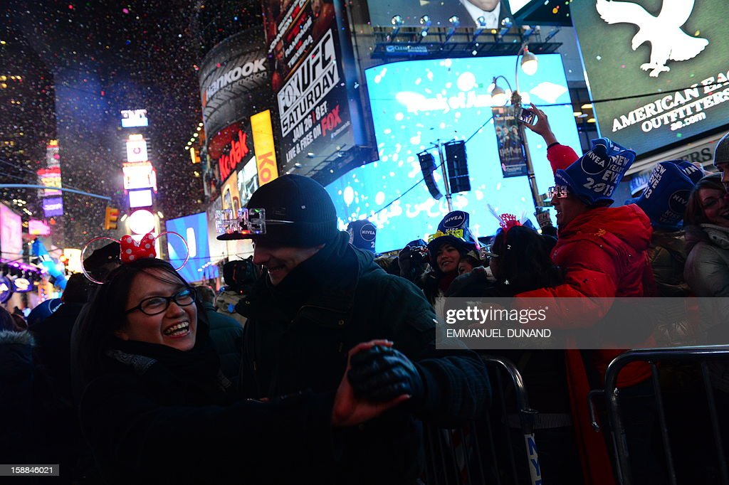 People celebrate the New Year on Times Square on January 1, 2013 in New York. A million people cheered in New York's Times Square as the traditional crystal ball dropped to mark the start of 2013, bringing a rolling global New Year's party that kicked off in Australia to US shores.
