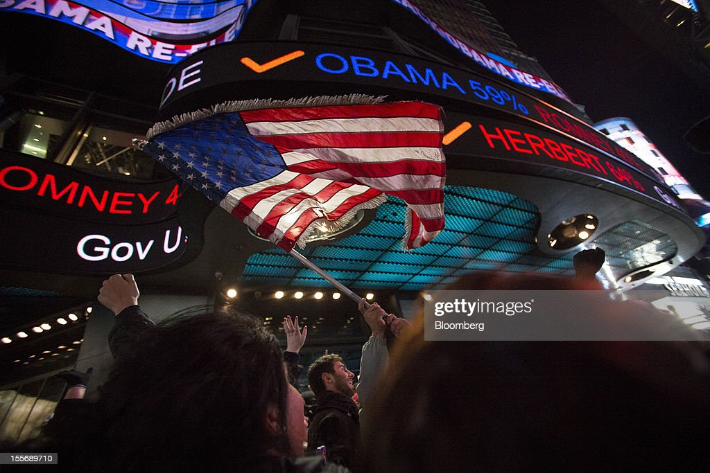 People celebrate the news that U.S. President Barack Obama has won re-election at Times Square in New York, U.S., on Wednesday, Nov. 7, 2012. Barack Obama, the post-partisan candidate of hope who became the first black U.S. president, won re-election today by overcoming four years of economic discontent with a mix of political populism and electoral math. Photographer: Scott Eells/Bloomberg via Getty Images