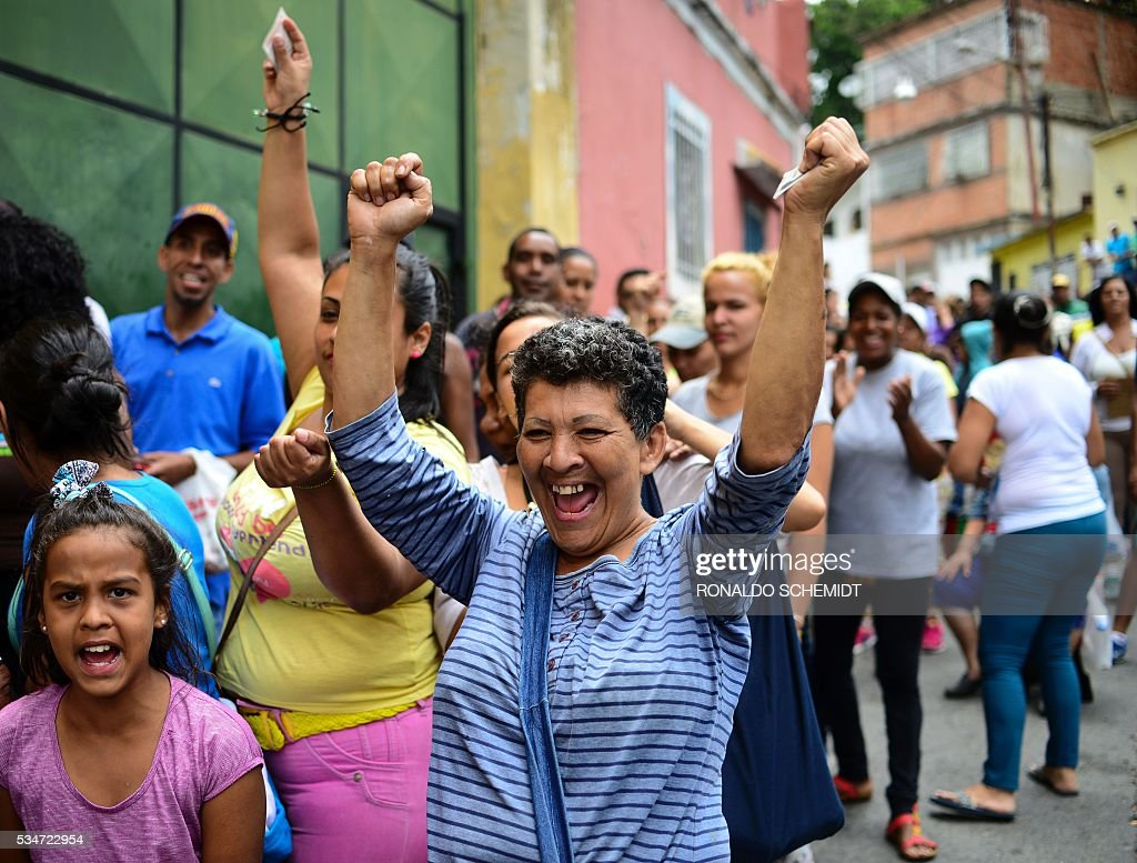 People celebrate when a truck with food arrives as they line up to buy basic food and household items outside a supermarket in the poor neighborhood of Lidice, in Caracas, Venezuela on May 27, 2016 / AFP / RONALDO