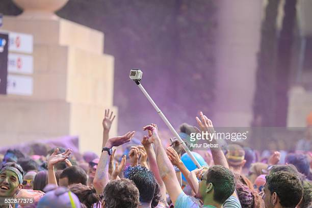 People celebrating a colorful powder party with Gulal holding a Gopro with stick selfie