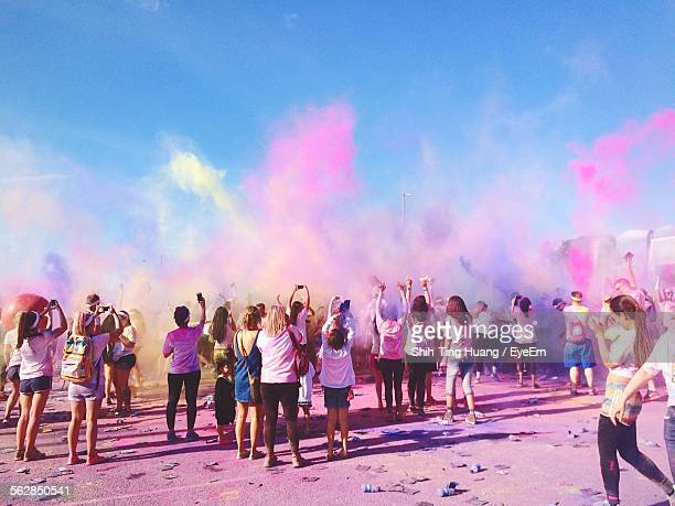 People Celebrating Holi Festival Outdoors Against Sky
