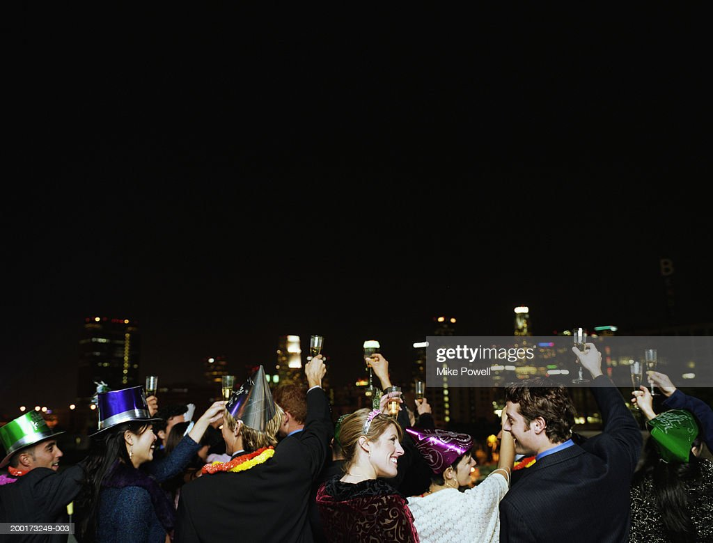 People celebrating on rooftop at New Years Eve party, rear view : Stock Photo