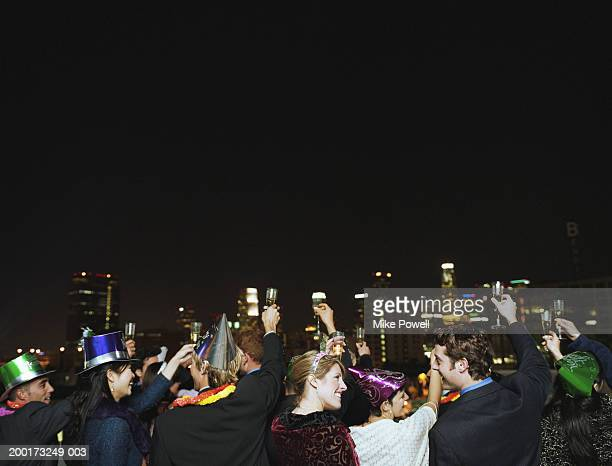 People celebrating on rooftop at New Years Eve party, rear view