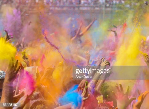 People celebrating the Holi festival with hands up