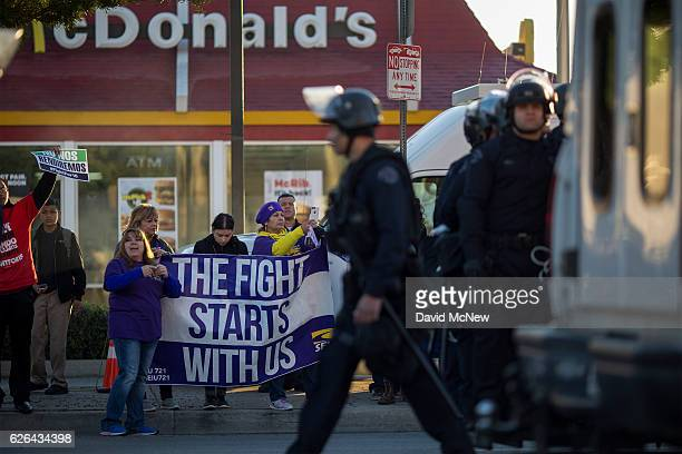 People chant as striking McDonald's restaurant employees are arrested and put onto buses for sitting in an intersection after walking off the job to...