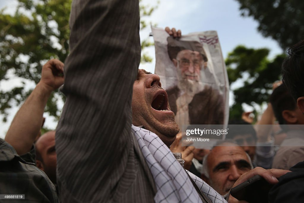 People chant 'death to America,' outside the shrine to the Ayatollah Khomeini on the 25th anniversary of his death on June 4, 2014 on the outskirts of Tehran, Iran. Thousands of people were bussed in from around the country to hear speaches marking the event. Khomeini, the founder of the Islamic Republic, is still revered by many Iranians, and his portrait hangs throughout the country.