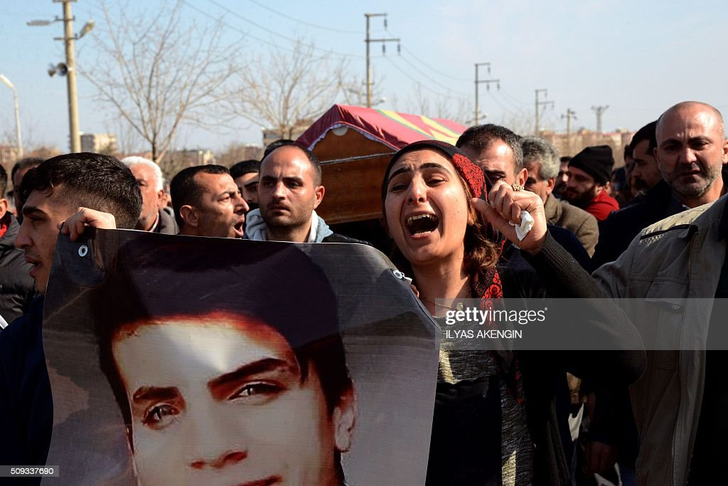 People chant slogans as they carry on February 10, 2016 in Diyarbakir the coffin of 16-year-old Mahmut Bulak, who was killed during a protest against operations in Cizre on February 9. Cizre has been under a controversial curfew for six weeks as the Turkish army pursues a relentless campaign against rebels of the PKK which activists claim has cost dozens of civilian lives. / AFP / ILYAS AKENGIN