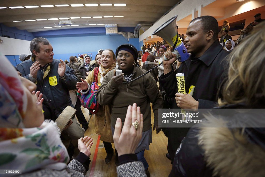 People chant slogans as they occupy a municipal gymnasium to demand that the Town hall make an effort to house them, on February 17, 2013 in Paris.