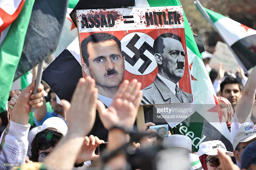 People chant slogans while holding a sign equating Syrian President Bashar al-Assad to Nazi dictator Adolf Hitler during a rally in support of the Syrian opposition at Lafayette Park in front of the White House in Washington on March 17, 2012. Several hundred people gathered to voice their opposition to the regime of Syrian President Bashar al-Assad and its brutal crackdown on the one-year uprising. AFP PHOTO/Nicholas KAMM