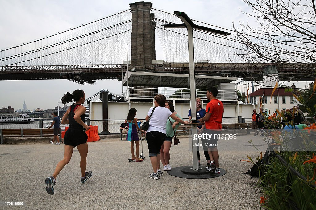 People charge their cell phones at a free solar-powered charging station set up by AT&T at Brooklyn Bridge Park on June 18, 2013 in the Brooklyn borough of New York City. Twenty-five solar-powered charging stations are being set up in parks, beaches and other spaces throughout New York City as part of the AT&T pilot project. The towers can accommodate six devices at a time with dedicated ports for iPhones, BlackBerrys and Androids, regardless of the wireless carrier.
