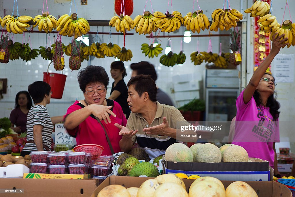 People chat at a fruit stall at a market in Singapore, on Sunday, Feb. 24, 2013. Singapore's Finance Minister Tharman Shanmugaratnam is scheduled to deliver the 2013 budget statement on Feb. 25. Photographer: Sam Kang Li/Bloomberg via Getty Images