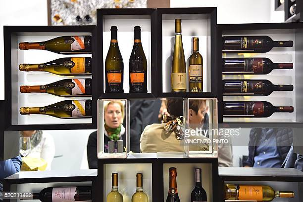 People chat behind wine bottles displayed on April 10 2016 during the 50th edition of the Vinitaly wine exhibition in Verona Vinitaly is the worlds...