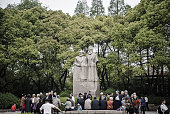 People chat in front of a statue of Karl Marx and Friedrich Engels at Fuxing Park in Shanghai China on Sunday April 10 2016 China's economy...