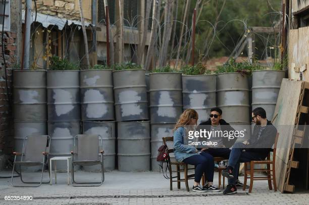 People chat over coffee next to a fortified position along the buffer zone on the southern Greek side of the divided city on March 7 2017 in Nicosia...