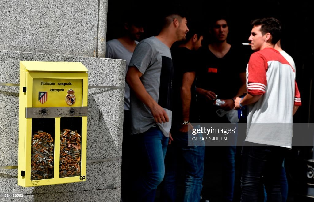 People chat past an ashtray displayed by the City Council, and shaped as a ballot box, inviting the passerby to vote with their cigarette butt for the next UEFA Champions League's winner, depicting the logos of both Madrid footbll teams, Atletico de Madrid (L) and Real Madrid, in Madrid on May 26, 2016. Real Madrid and Atletico de Madrid will play the Champions League final football match on May 28, 2016 in Milan. / AFP / GERARD