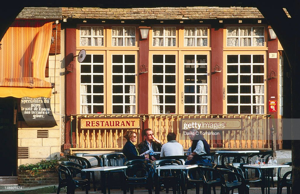 People chatting outside restaurant in main square, late afternoon, Lyons-la-Foret, Eure. : Stock Photo