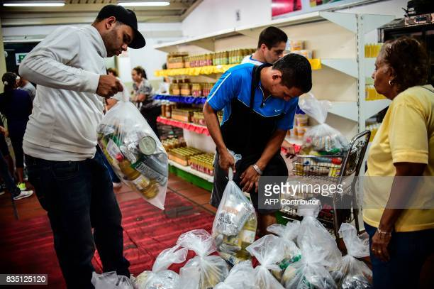 People check bags of foodstuff inside one of the food distribution centers called CLAP which are run by community leaders in Caracas on August 16...
