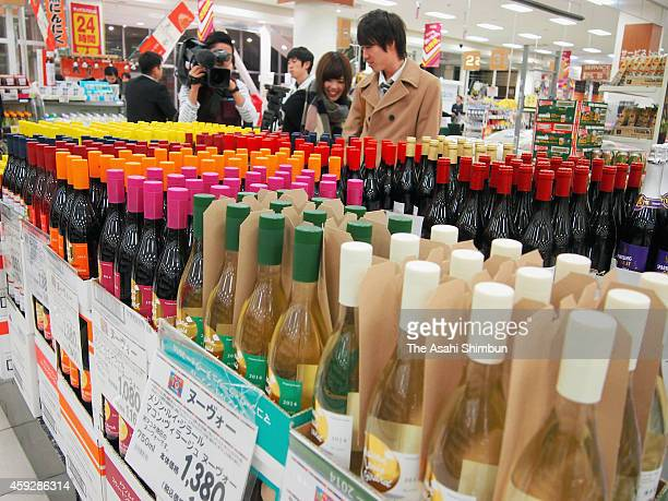 People check bottles of Beaujolais Nouveau after its release at a supermarket on November 20 2014 in Nagoya Aichi Japan The import of the wine used...