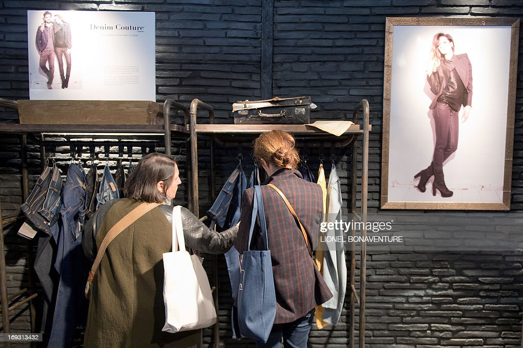 People check clothes at the Tavex booth during the denim jeans fair on May 22, 2013 in Paris.
