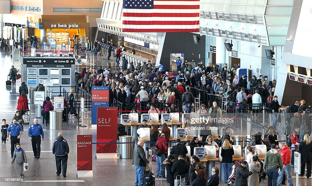 People check in and line up for security as Logan Airport is reopened for the first full day, on Sunday, February 10, 2013, after the blizzard.
