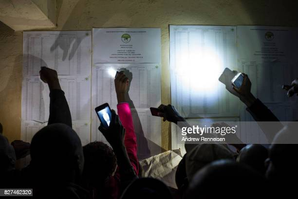 People check names on a voter registration list at the Olympic Primary School in Kibera one of the largest slums in Africa on August 8 2017 in...
