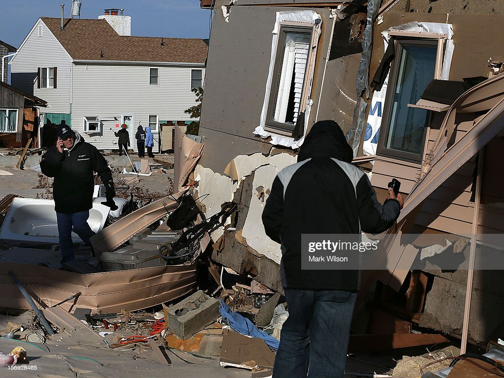 People check out a home damaged by Superstorm Sandy on November 25, 2012 in Ortley Beach, New Jersey. New Jersey Gov. Christie estimated that Superstorm Sandy cost New Jersey $29.4 billion in damage and economic losses.