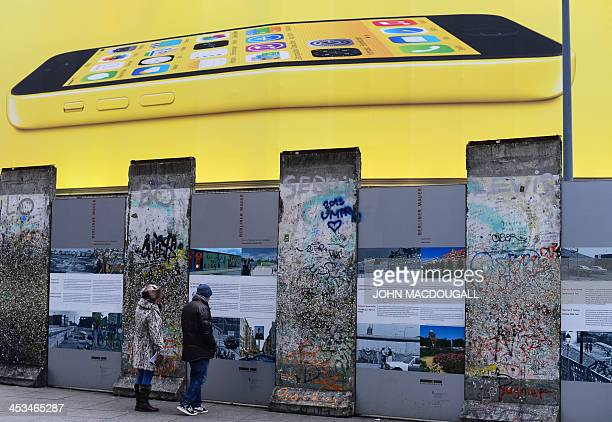 People check out a segment of the Berlin wall at Potsdamer Platz as a giant billboard advertises an iPhone 5C in Berlin December 4 2013 AFP PHOTO /...